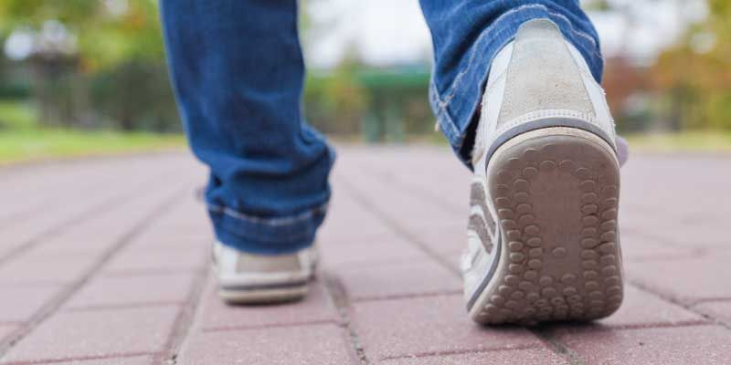 Teenager walking in sport shoes on pavement