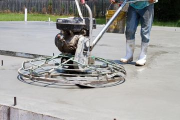 Construction worker uses a motorized power trowel to smooth and finish a concrete slab at a new home job site